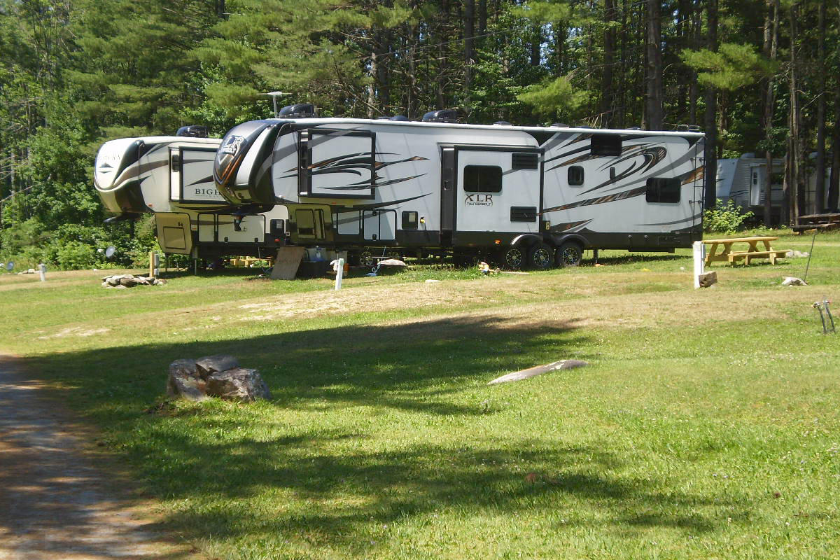 Two RVs in sunny campsites
